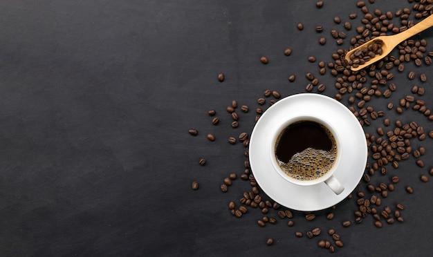 검은색 나무 탁자 위에 있는 커피와 콩 한 잔