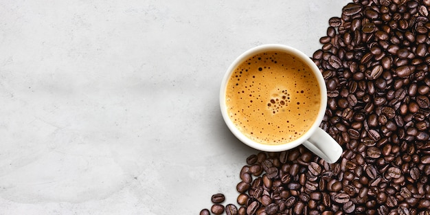 一杯のコーヒーとセメントテーブル背景に豆