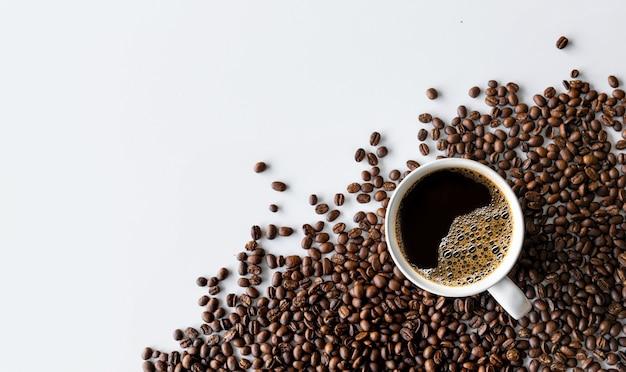 白いテーブルの背景にコーヒーと豆のカップ。上面図