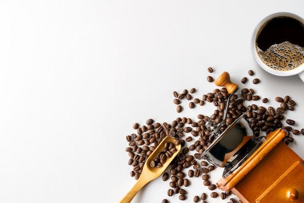 Чашка кофе и бобов на белом фоне таблицы. вид сверху