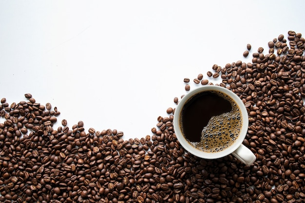 Чашка кофе и бобов на белом столе