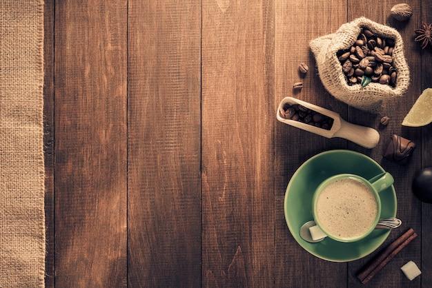 木製の背景にコーヒーと豆のカップ