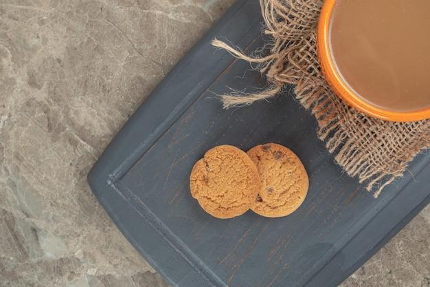 Чашка кофе и печенье на темной тарелке.