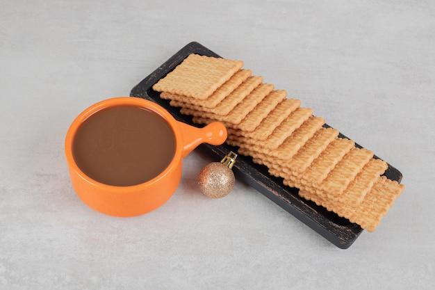 大理石の表面にコーヒーとビスケットのカップ