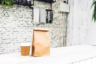 Cup of coffee and blank paper bag with copy space for your brand on table