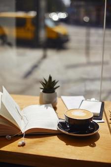 窓際のカフェのテーブルで一杯のコーヒーと本