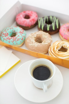 Cup of coffee and box of doughnuts