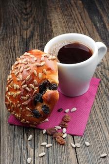 木製のテーブルにひまわりの種とレーズンとコーヒーとパンのカップ