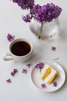 白いテーブルの上にライラックの花束、コーヒー、ケーキのプレートと一緒に、一杯のコーヒーとケーキの角が静物から生まれました。 3月8日国際女性の日