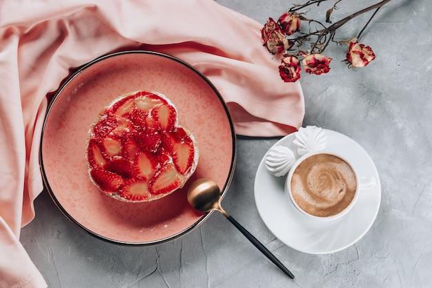 灰色のテーブルにイチゴとコーヒーとケーキのカップ