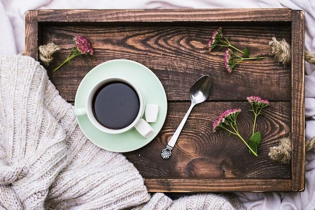 소박한 나무 서빙 트레이와 뜨개질 따뜻한 모직 스웨터에 커피와 촛불의 컵