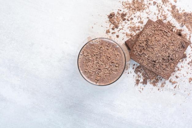 Чашка кофе и шоколадный батончик с какао-порошком. фото высокого качества