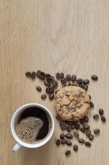 木製の背景にコーヒーとチョコレートチップクッキーのカップ