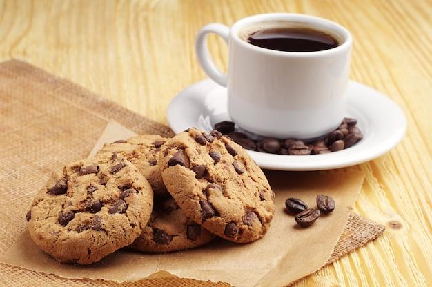 テーブルの上のコーヒーとチョコレートクッキーのカップ