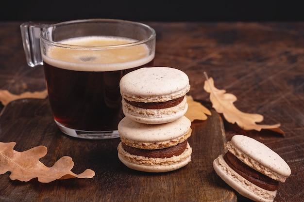 나무 배경에 커피와 초콜릿 마카롱 한 잔. 아늑한 가을 구성입니다. 유리 컵에 담긴 뜨거운 에스프레소 - 이미지