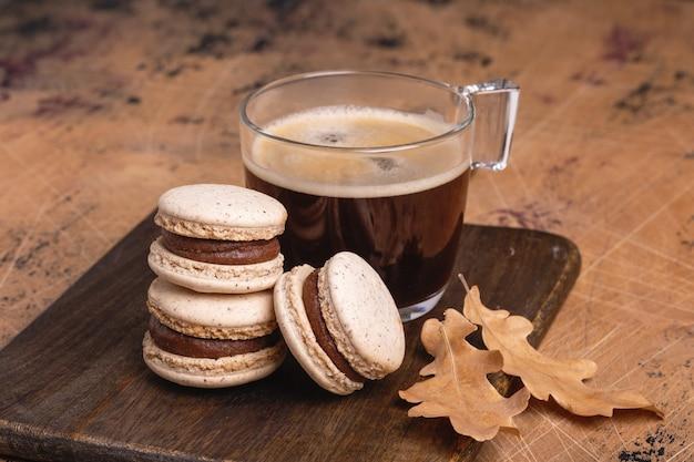 나무 배경에 커피와 초콜릿 마카롱 한 잔. 아늑한 가을 구성 - 이미지