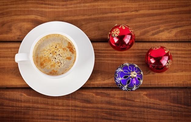 나무 배경에 커피와 크리스마스 거품 한 잔.