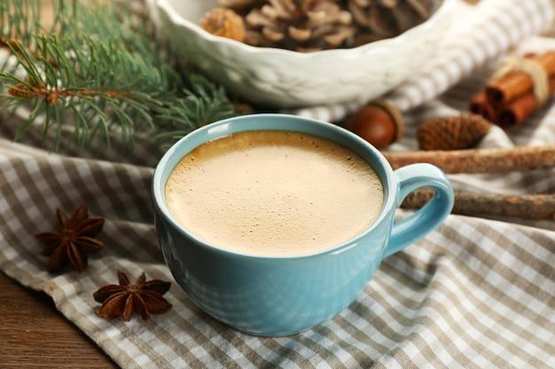 一杯のコーヒーとナプキンのクリスマスツリーの枝、クローズアップ