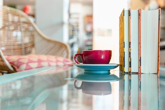 Cup of coffee and closed book on reflective glass table