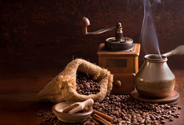 Чашка кофе и кофейных зерен в мешке на темном фоне, вид сверху