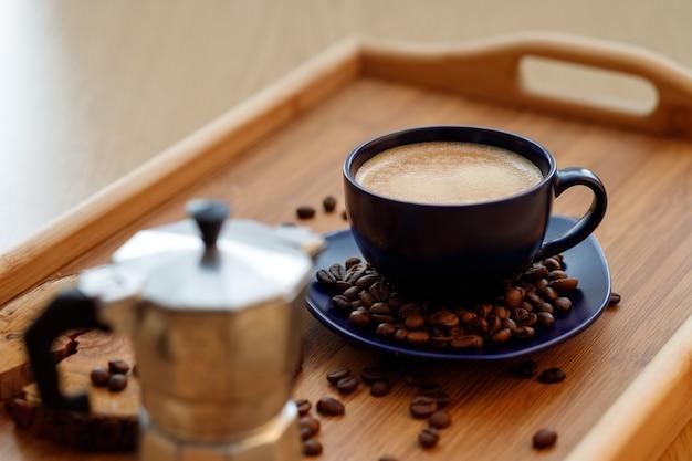 Чашка кофе и кофейных зерен на блюде и гейзерная кофеварка на деревянном подносе