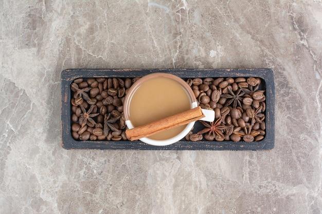 Чашка кофе и кофейных зерен на темной тарелке. фото высокого качества