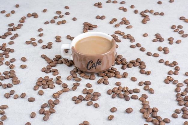 大理石の背景にコーヒーとコーヒー豆のカップ。高品質の写真