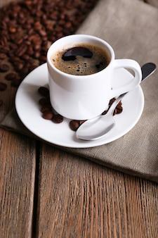 나무 바탕에 냅킨에 커피와 커피 콩의 컵