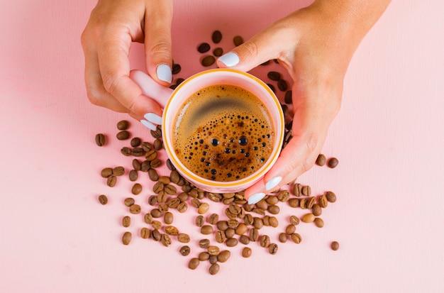 一杯のコーヒーとピンクの表面にコーヒー豆