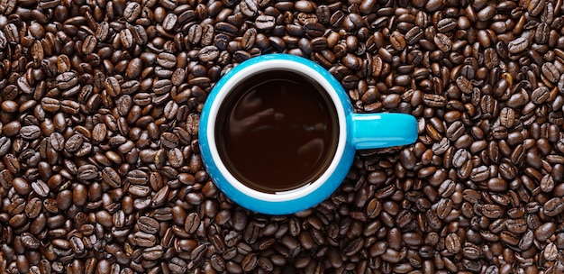 一杯のコーヒーとコーヒー豆。上面図、フラットレイ。