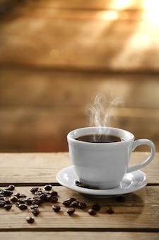 一杯のコーヒーと木製の背景にコーヒー粒