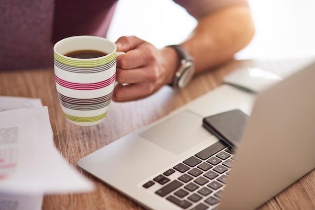一杯のコーヒーとコンピューターのキーボード