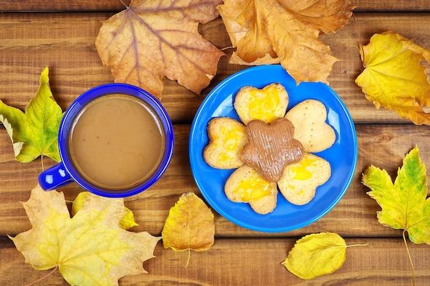 마른 가을 잎이 있는 테이블에 커피와 쿠키 한 잔. 가을의 마른 잎으로 둘러싸인 나무 탁자에서 가을에 마시는 커피