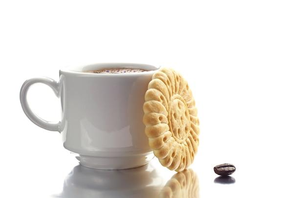 白い背景に反射とコーヒーとクッキーのカップ。セレクティブフォーカス。