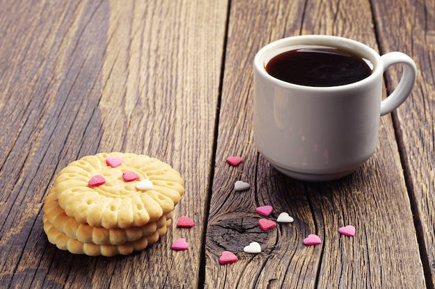 ヴィンテージの木製テーブルに小さな甘い心とコーヒーとクッキーのカップ