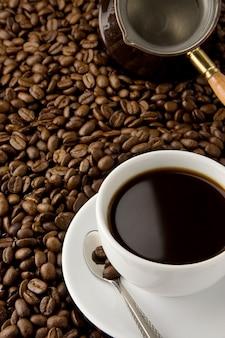 Чашка кофе и медный горшок на бобах