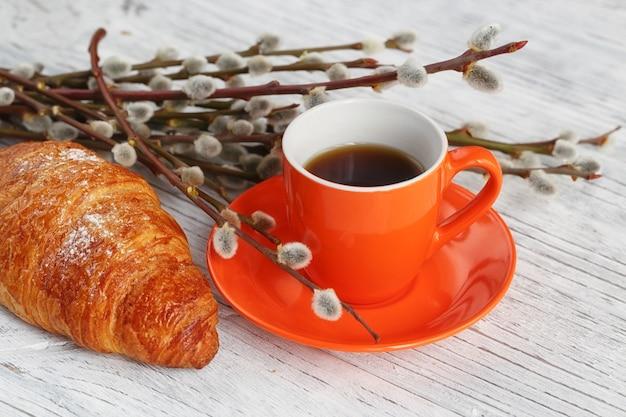 흰색 나무 테이블에 갯버들과 커피와 크루아상 컵. 낭만적 인 분위기