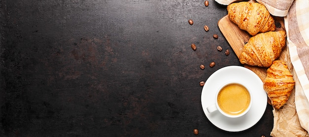 古い素朴な背景に置かれた木の板の上に立っているコーヒーとクロワッサンのカップ