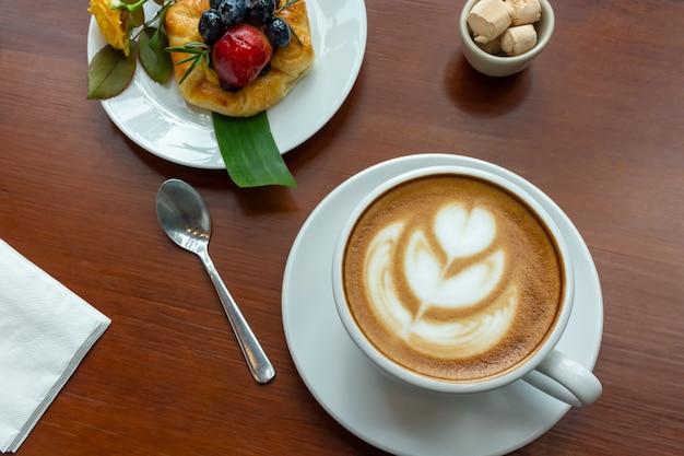 Чашка кофе и датская булочка с ягодами на деревянном столе.
