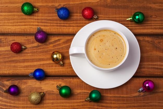 나무 배경에 커피 한 잔과 다른 크리스마스 거품이 있습니다.