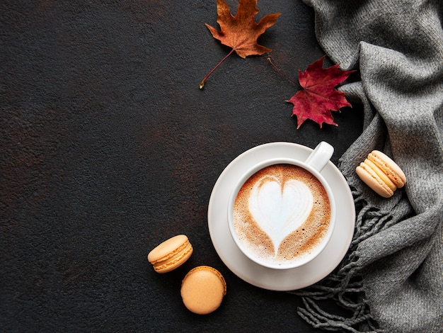 黒いコンクリートの上にコーヒーと乾燥した葉のカップ。