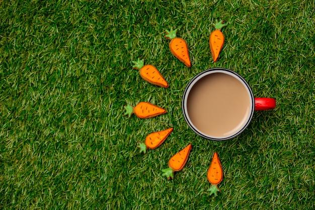 緑の草の上のコーヒーとイースターニンジンクッキーのカップ