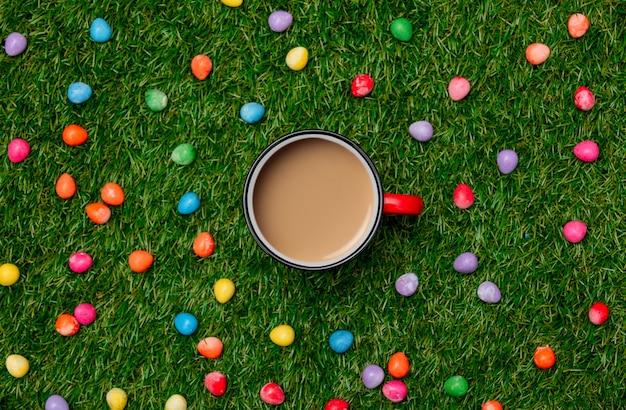 緑の草の上のコーヒーとイースターチョコレートの卵のカップ