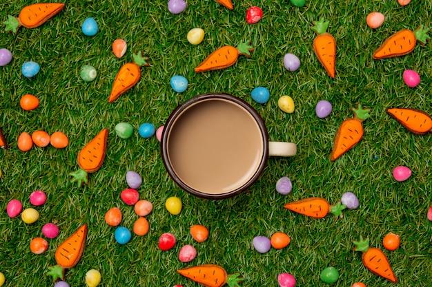 緑の草の上にクッキーニンジンとコーヒーとイースターチョコレートの卵のカップ