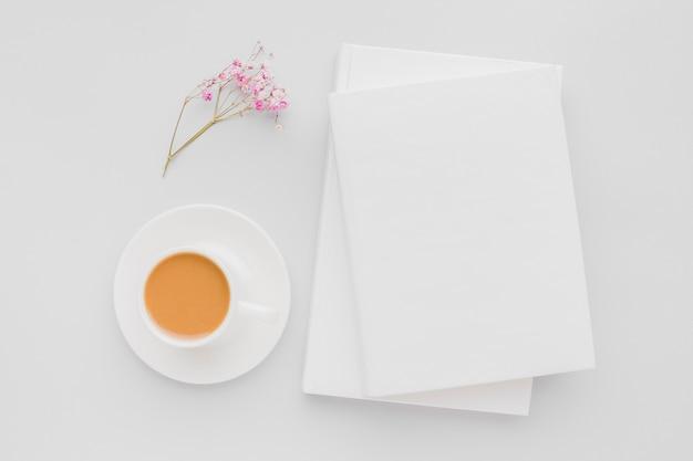 本の横にある一杯のコーヒーと花