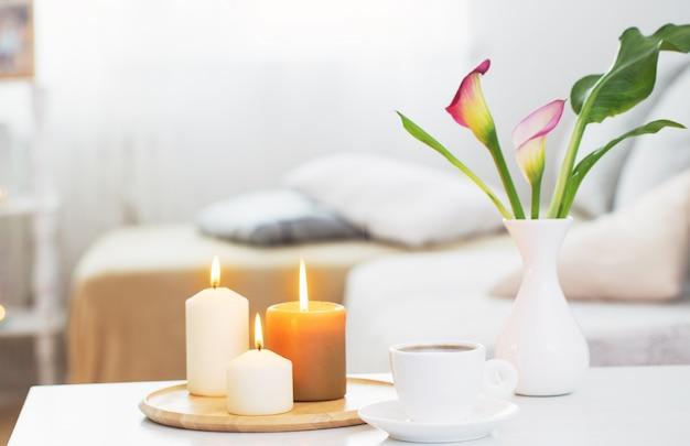 屋内の白いテーブルの上に花瓶にコーヒーと花のカップ