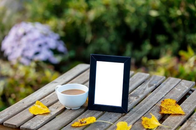 Чашка кофе и рамка для картины на столе в саду