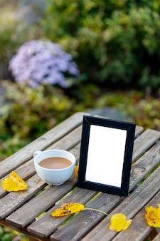 정원에있는 테이블에 그림을위한 커피와 프레임 컵