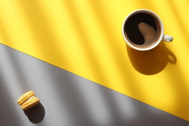 深い影とトレンディな黄色と灰色の背景にコーヒーとフレンチペストリーマカロンのカップ Premium写真