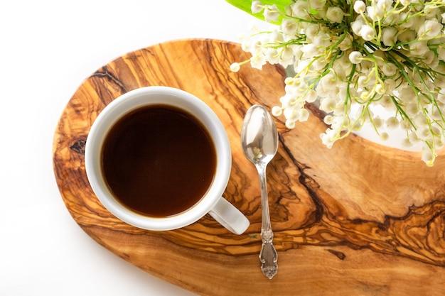 一杯のコーヒーと木製のスタンドに咲くスズランの花の新鮮な花束